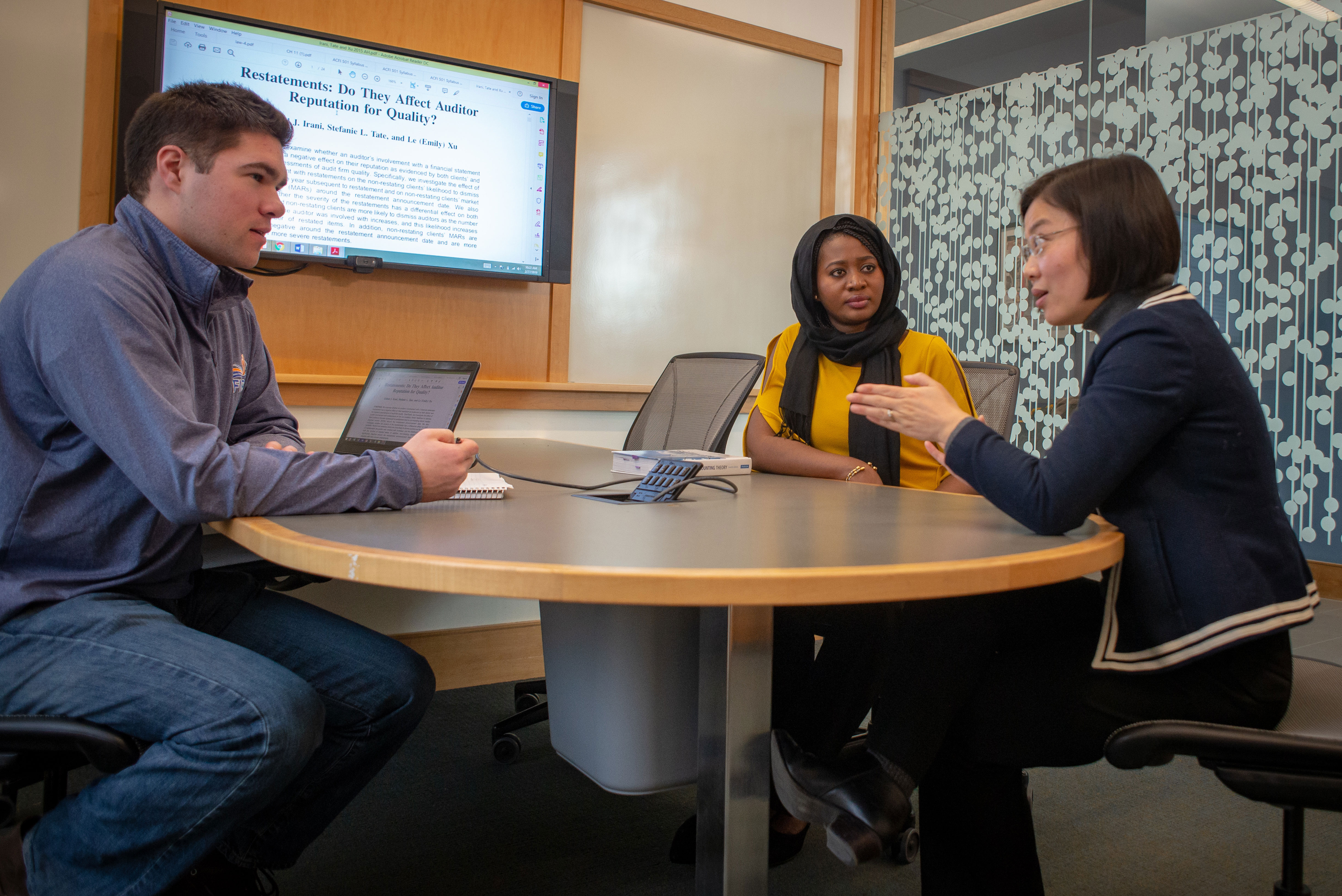 students in an masters accounting discussion with a faculty member