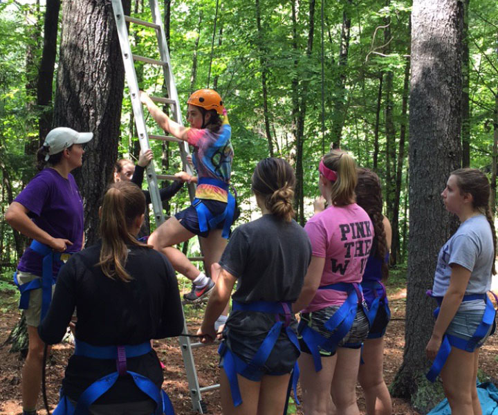 Student in harness climbing ladder to get to high ropes course while other students look on