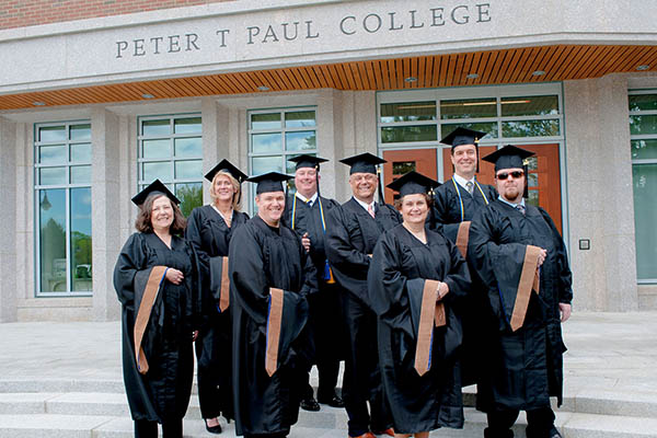 paul college alums in graduation gowns