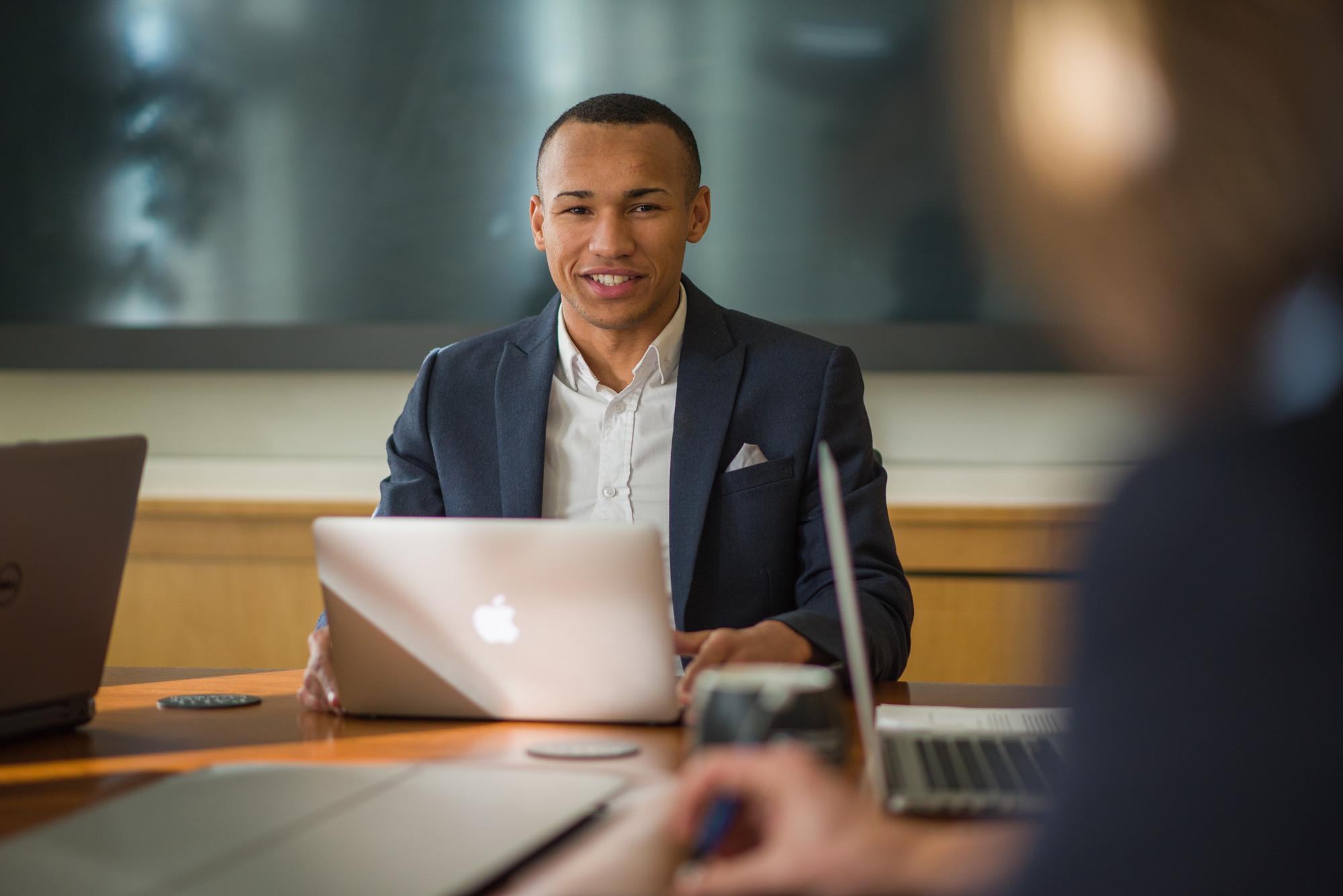 UNH Full-time MBA student Dante Lamb works at conference table with laptop