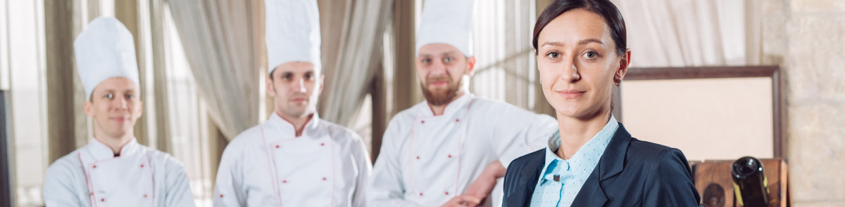 Woman in business attire and men in chef uniforms