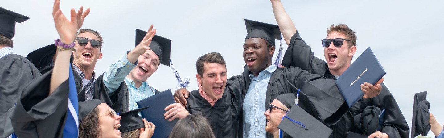 Students at commencement ceremony celebrating with hands in the air