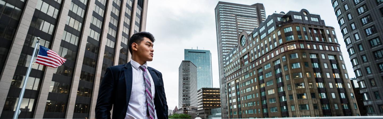 Ashim Gurung '22 stands outside along a Boston skyline