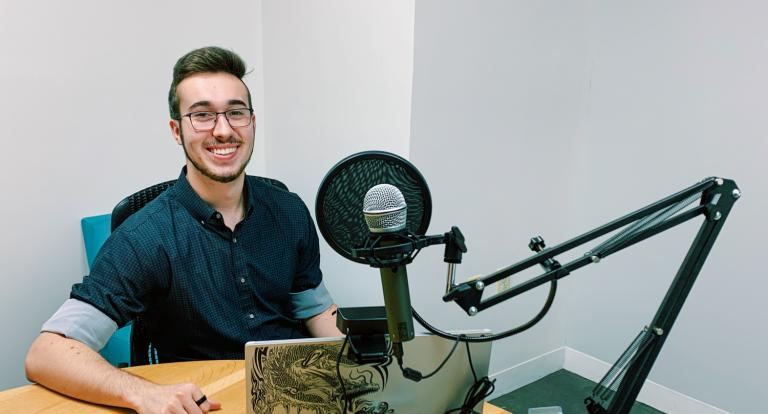 A male student seated at a table poses with his laptop and podcasting equipment