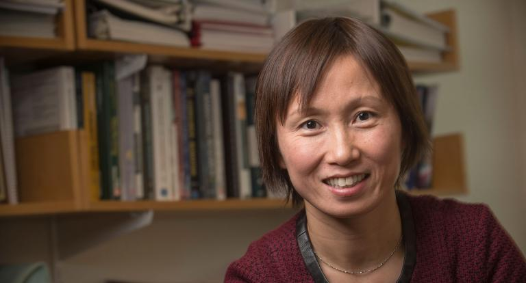 Shuili Du close up with bookshelves behind her