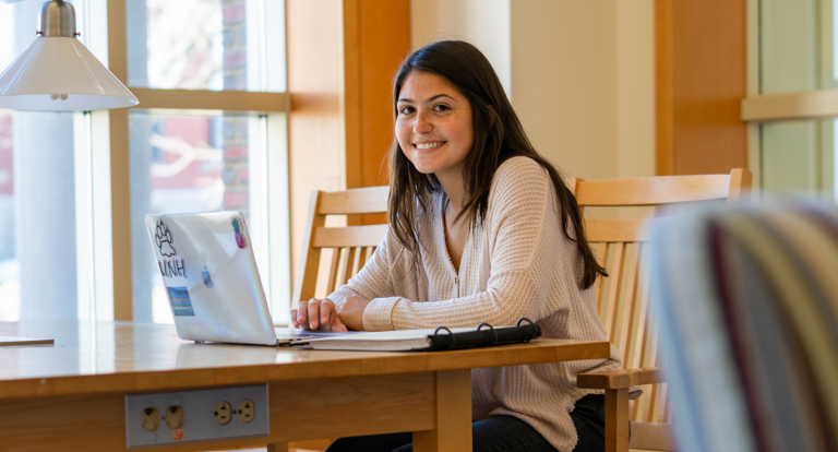 A female student sits at a table in the UNH library with her laptop and backpack, smiling at the camera.