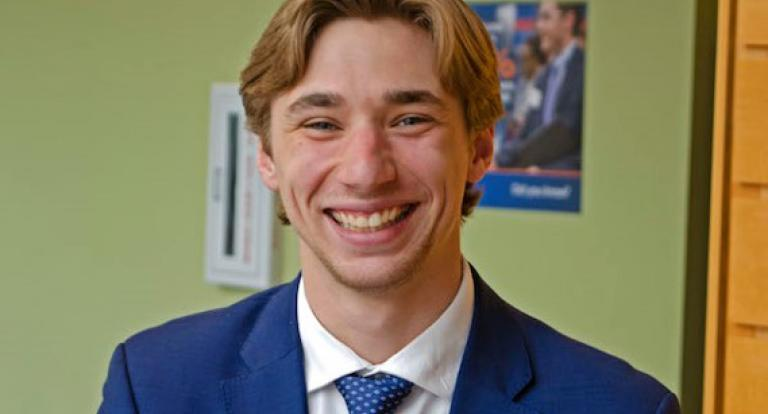A male student wearing business attire smiles at the camera.