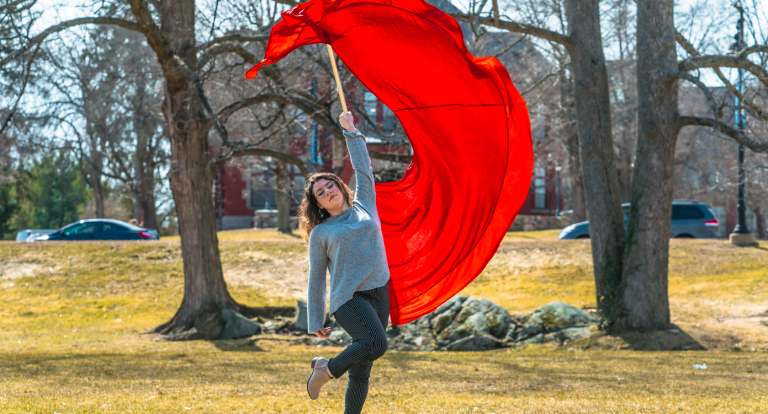 A student swinging a large red color guard flag