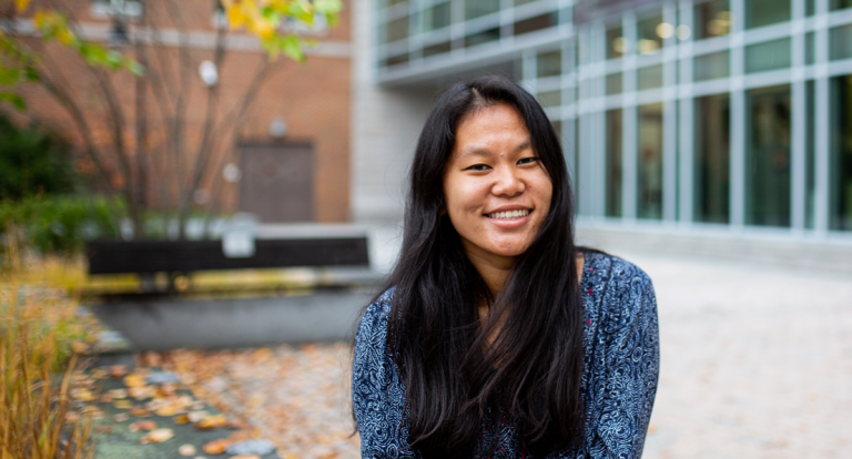 A female student sits in Paul College's outdoor courtyard, smiling at the camera.