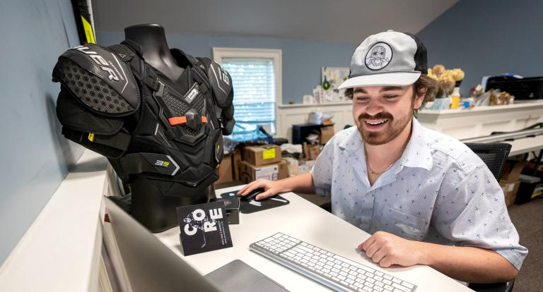 Ryan Meader '22 works at his laptop next to a mannequin wearing Helios Hockey technology.