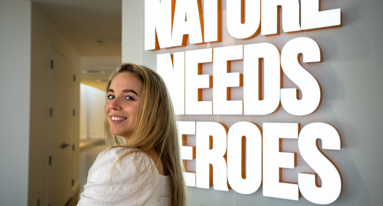 """Katie Rascoe '22 poses in front of neon sign that reads """"Nature needs heroes"""" in Timberland's lobby."""