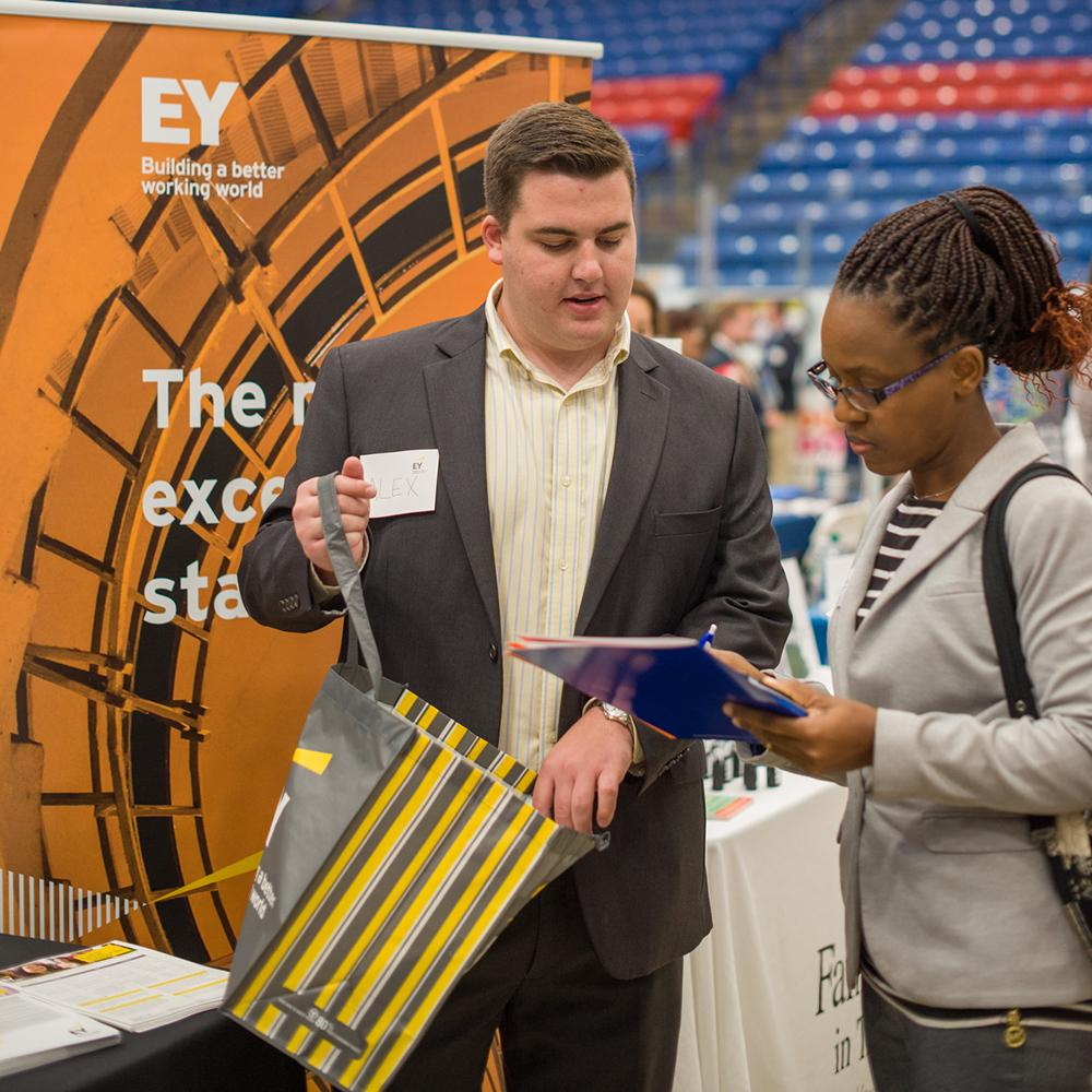 EY Recruiter talks to student at UNH Career Fair